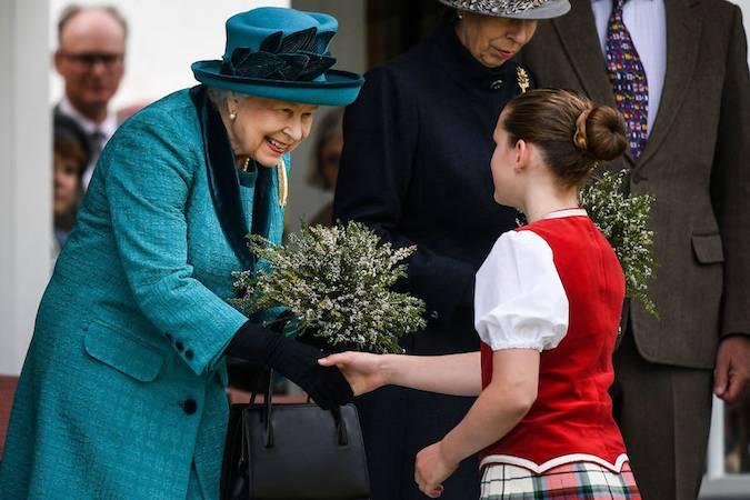 Монарх получает красивый букет цветов от молодой девушки, с которой она даже немного поболтала.